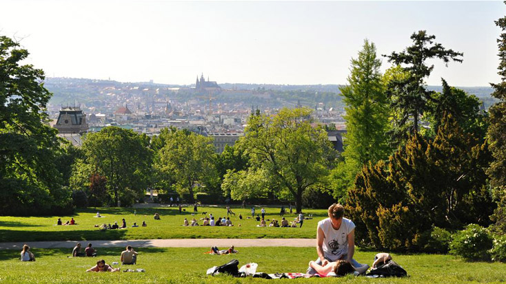 Young people enjoy the sunshine with a view of the Castle and Old Town at Riegrovy Sady